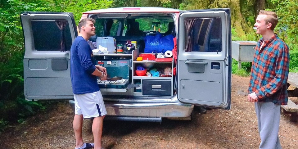 Two men cook breakfast by their camper-van.