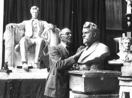 Photo of Daniel Chester French at work in his studio, with his sculpture of the seated Abraham Lincoln in the background