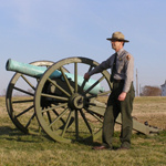 A ranger stands next to a cannon at Malvern Hill battlefield