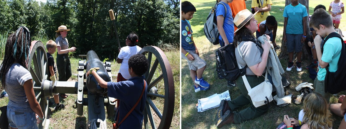 Two female park rangers guide school children in loading a Civil War cannon.