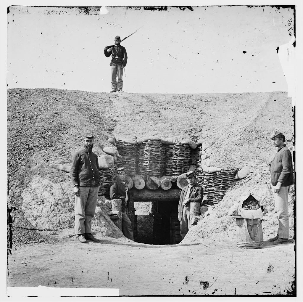 Historic image of four Union soldiers posing at the entrance of the Fort Harrison magazine. Another armed soldier stands on top of the magazine.