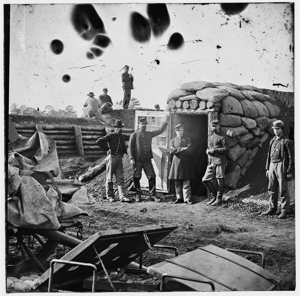 A historic image of the inside of Fort Harrison, circa 1864-1865. A group of five soldiers pose near the door of the bombproof.