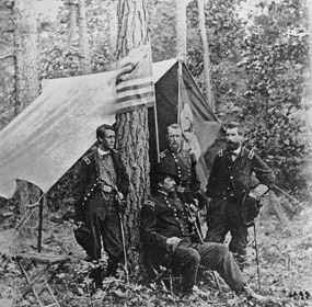 Four officers of the Union army, three standing, one seated, in front of a shelter.