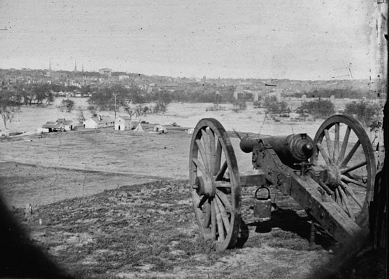 A cannon in the foreground looks toward Richmond skyline during the American Civil War.