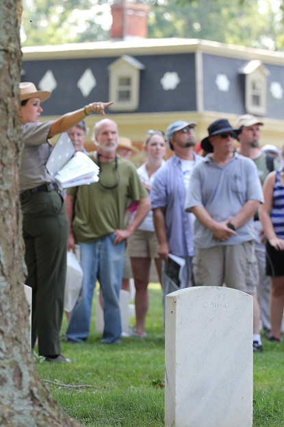 A uniformed park ranger gestures while standing among gravestones and park visitors