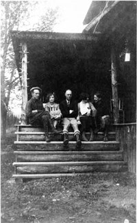 McGraw family members sit on the main house front porch.