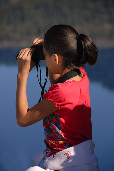 A student peers through binoculars into Crater Lake.