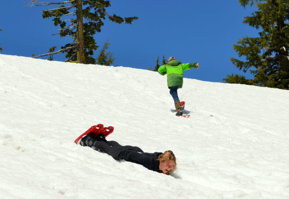 Students slides down a snowy slope at Crater Lake.