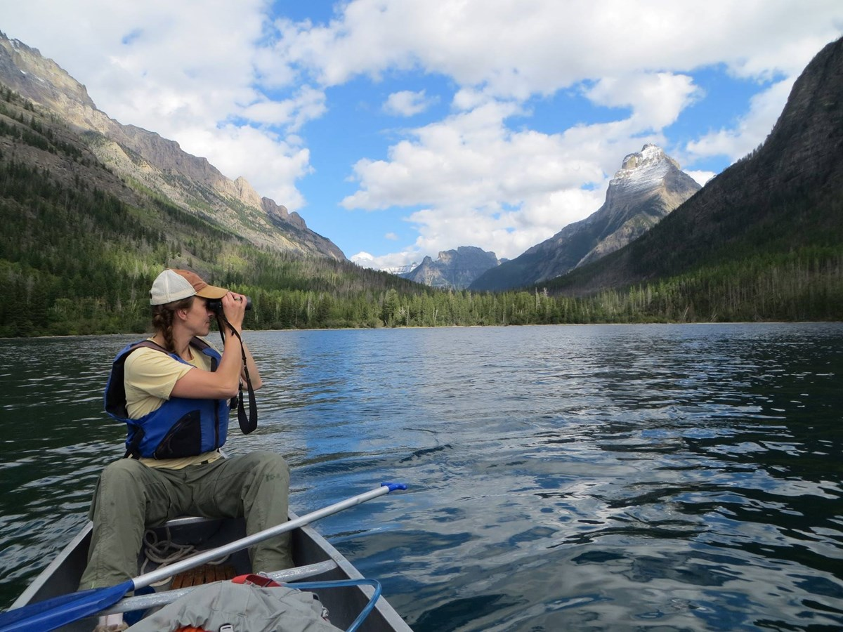 Citizen scientist sits in a canoe and scans for loons.