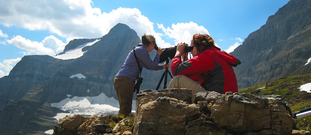 Two women scan mountainside for mountain goats; one looks through scope, the other through binoculars.