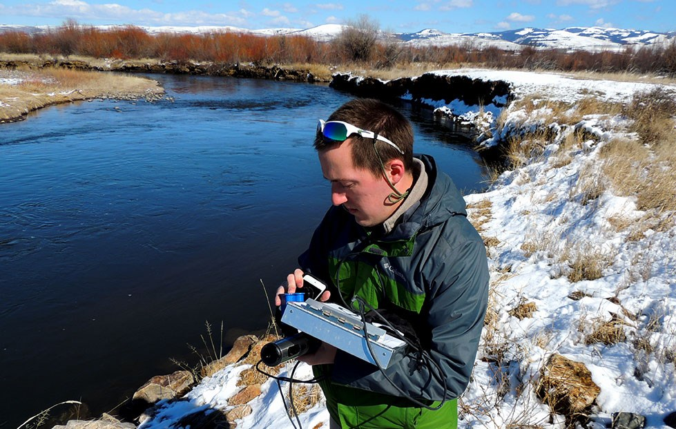 Jerry O'Neal research fellow Andrew Spencer stands by river holding monitoring equipment.