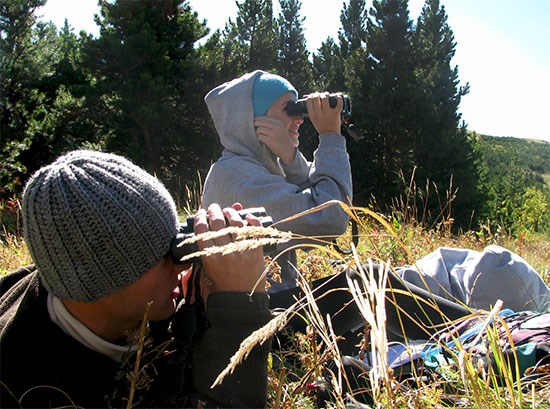 Two high school students sit in meadow looking through binoculars.