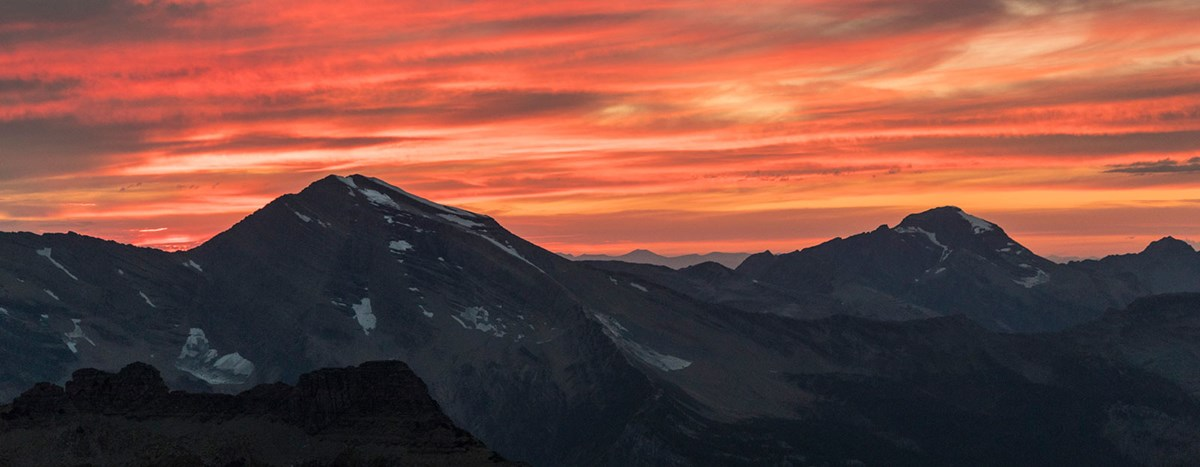 Pink and orange sunset over the peaks of Glacier.