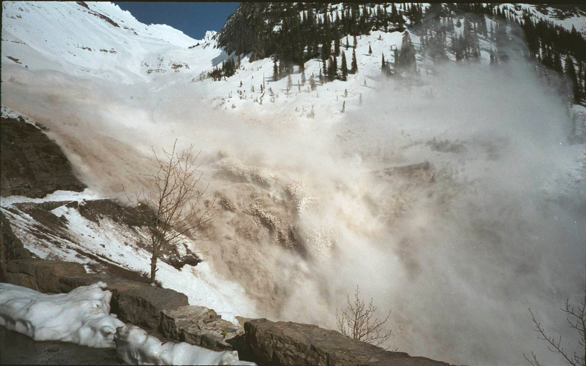 A cloud of snow and debris rises from an avalanche ripping down the mountainside over the Going-to-the-Sun Road.