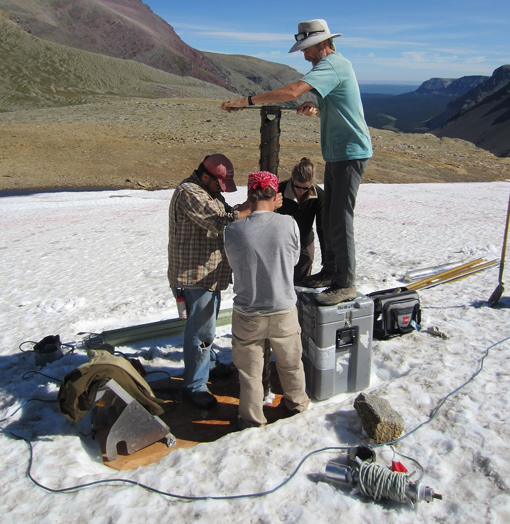 Crew of four uses hand-driven auger on snowfield