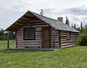 Restored log cabin with pitched roof and small porch
