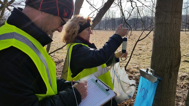 A woman prepares to weigh a bag of maple sap while a man notes the tree number on a data sheet.