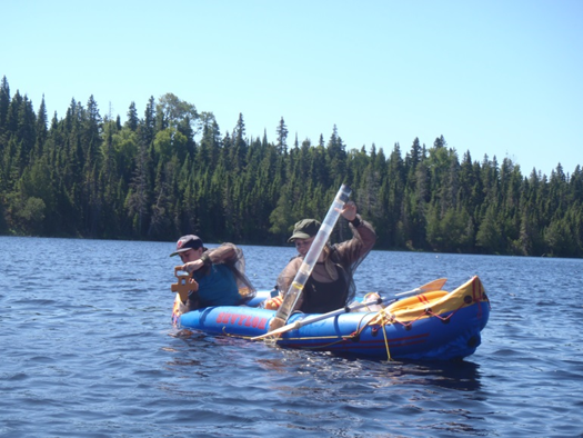 Two field technicians lower instruments over the edge of an inflatable boat and into the water.