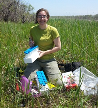 Researcher kneels at the edge of a wetland and prepares equipment for plant sampling.