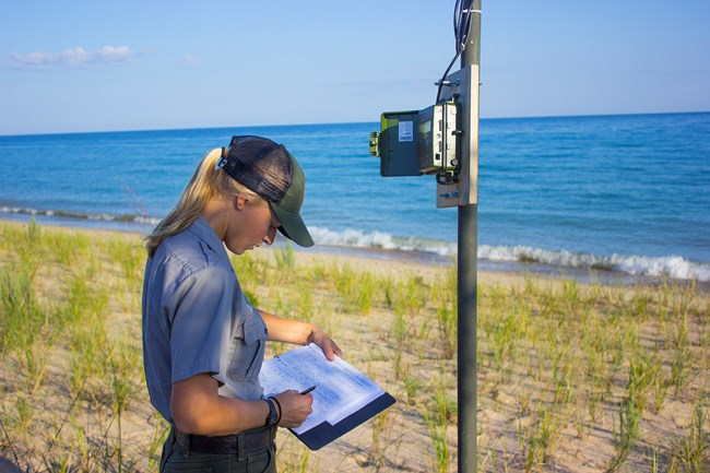 A woman in a National Park Service uniform stands next to a monitoring device mounted on a pole. She is recording data on a clipboard.