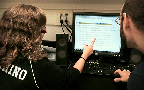 Two students look at a spreadsheet on a computer screen.