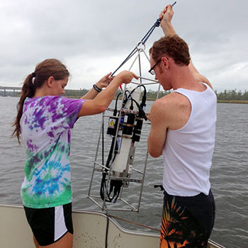 Two students remove water quality testing equipment from the water.