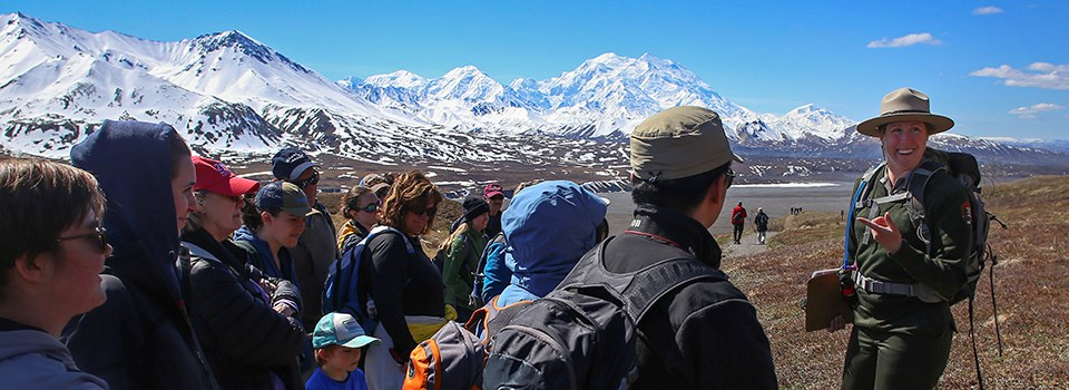 ranger speaks with large group in front of mount denali