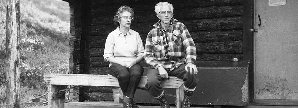black and white photo of a man and woman sitting on a porch