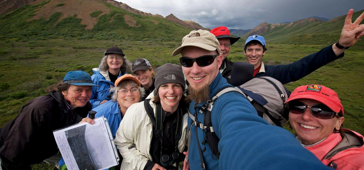 a group of hikers smile excitedly