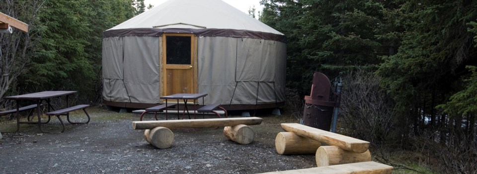 a yurt surrounded by benches and picnic tables