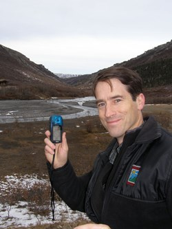 man holding a small electronic device, a river and hills in the background