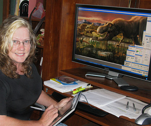 woman in front of a computer which shows a digital dinosaur illustration