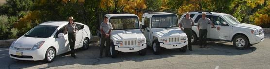 Park staff members stand with energy efficient vehicles
