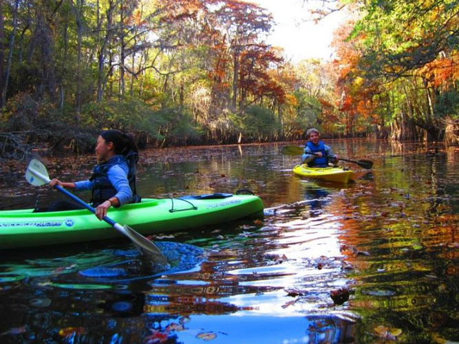 Two interns kayak on the Chattahoochee River on an Autumn day