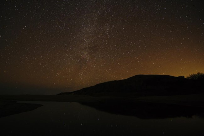 The Milky Way visible over a creek flowing across the beach and into the ocean, with light pollution also obvious on the horizon