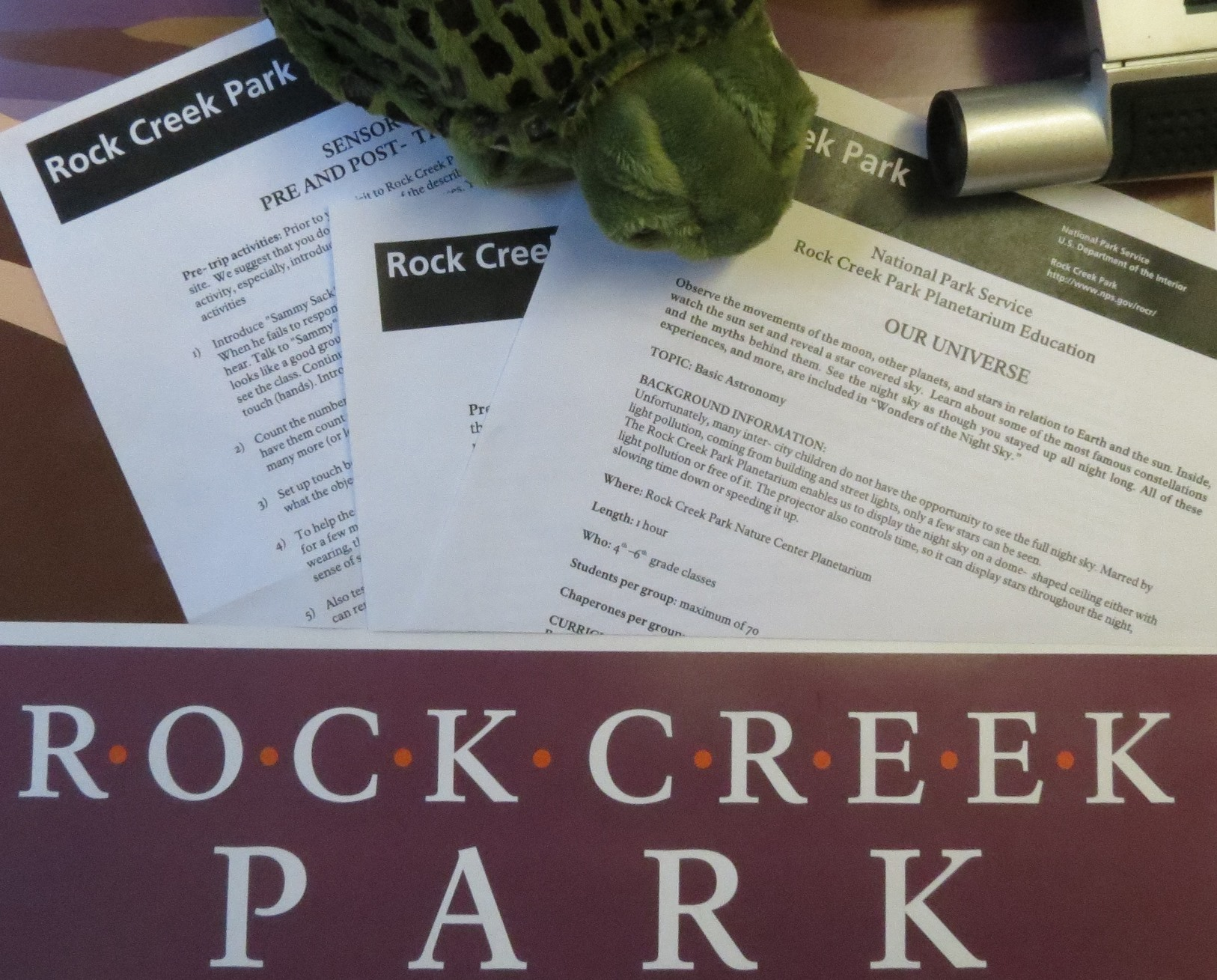 A turtle, lesson plans and Rock Creek Park logo spread on a table