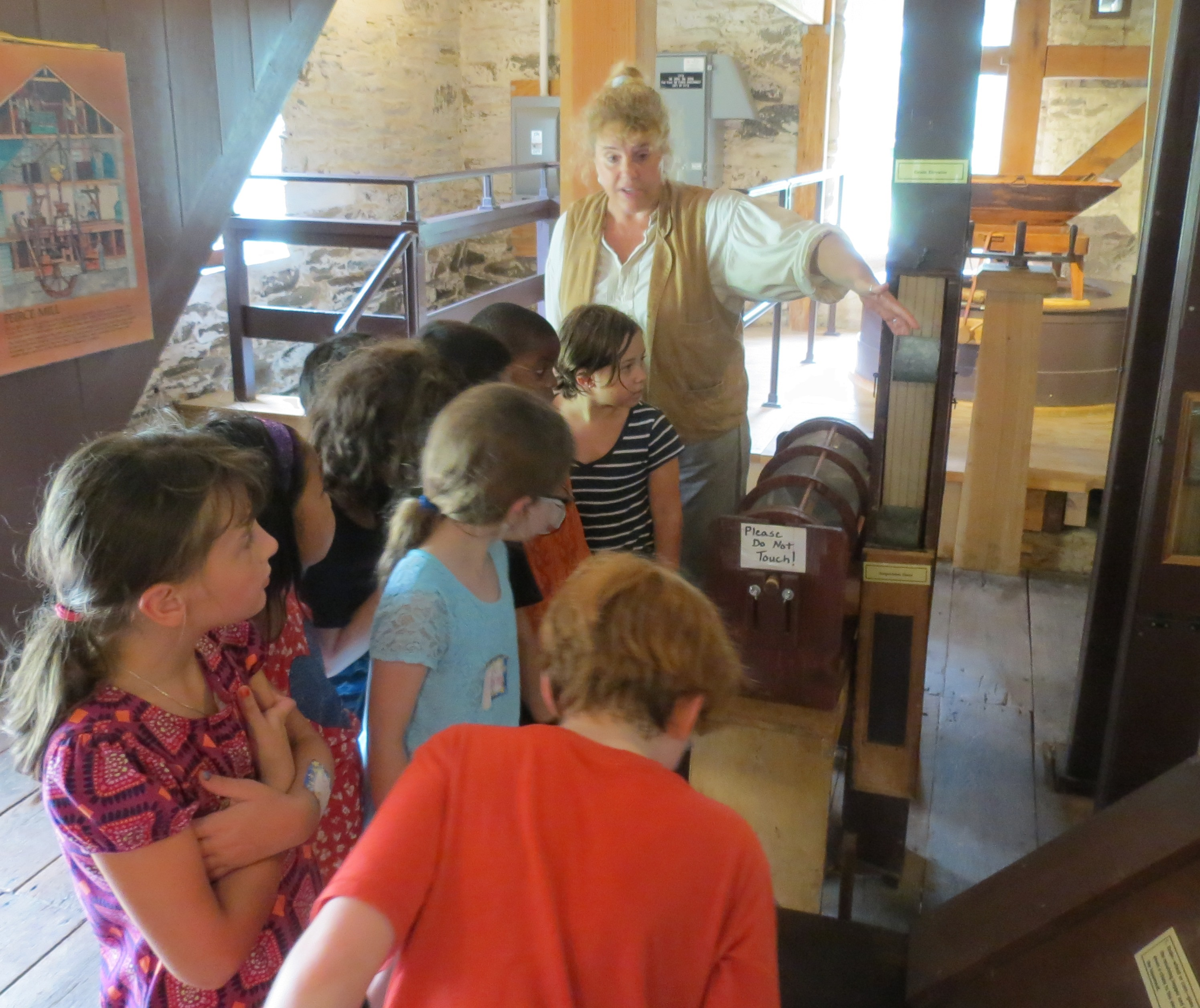 Miller Jeanne shows kids how the bolter separates different sizes of grain