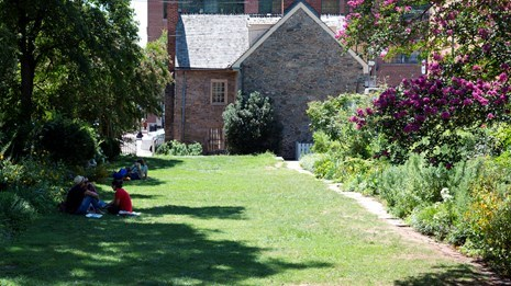 People sit on a mowed lawn surrounded by flowers in the Old Stone House back yard.