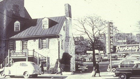 Black and white photo of old stone house with a car parked in front