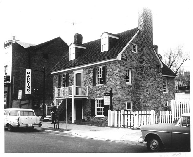 Black and white photo of Old Stone House with a uniformed park ranger standing in front.