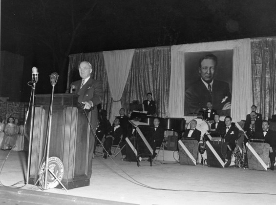 President Truman speaks at a podium with a large portrait of Carter Barron behind him.