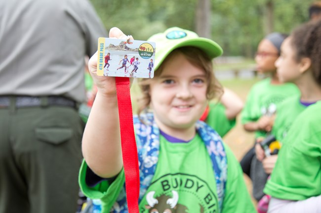 A young girl shows off her Every Kid in a Park badge during an event.