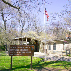 "An image of the front of the Nature Center in spring, including the sign outside which reads, ""Rock Creek Park Nature Center and Planetarium"""