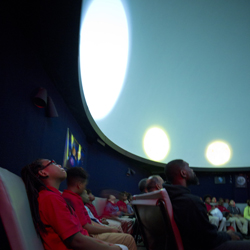 Children look up at the planetarium ceiling, which displays stars relative to one another's size.