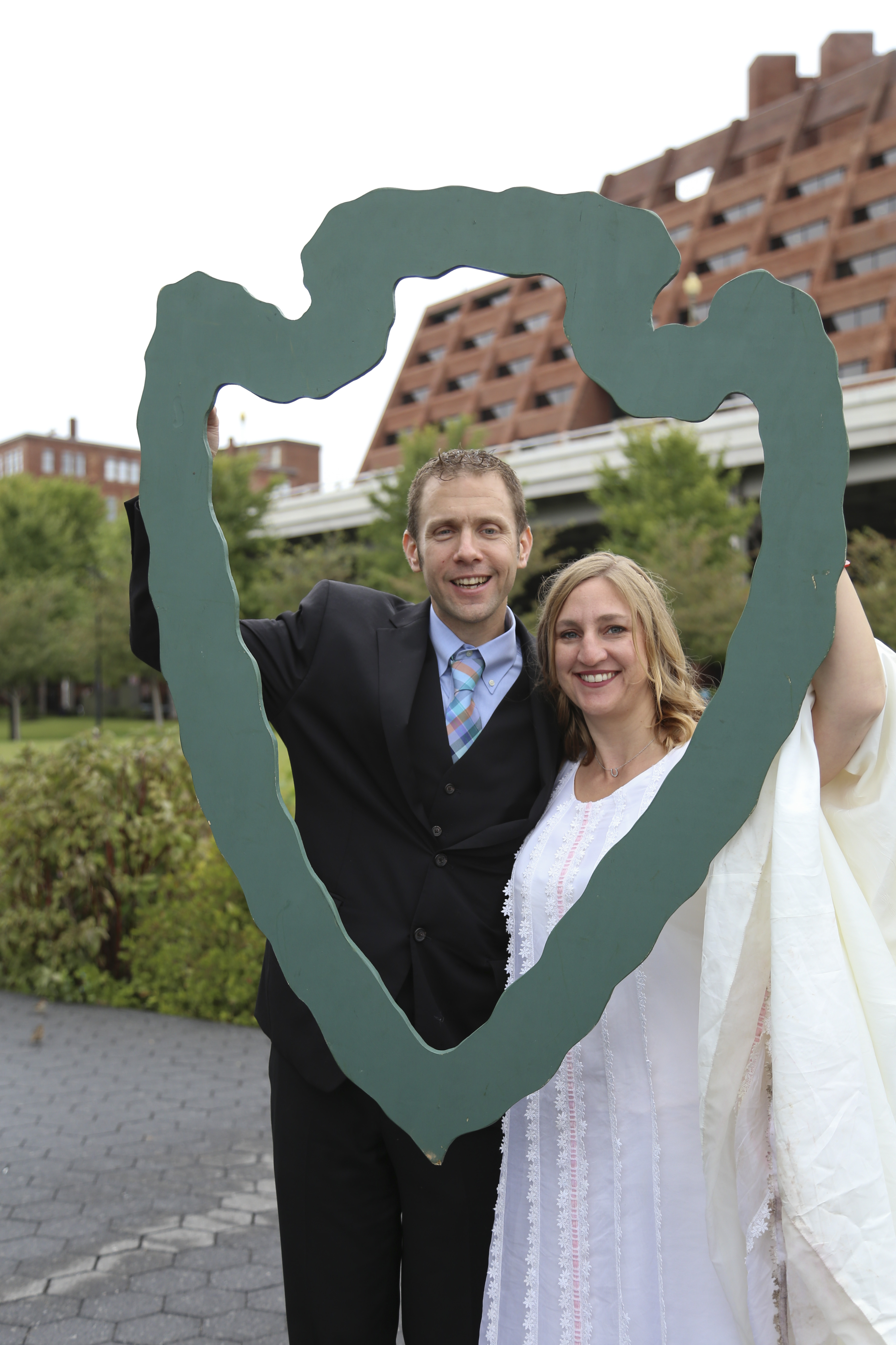 A man and woman in wedding attire hold up a wooden NPS arrow as a photograph is taken of them at Georgetown Waterfront Park in Rock Creek Park.