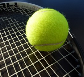 A generic tennis ball resting on a tennis racket.