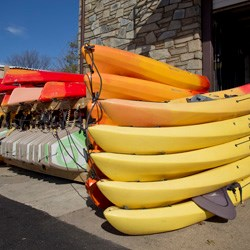 Kayaks piled on-top of each other at the Thompson Boat Center