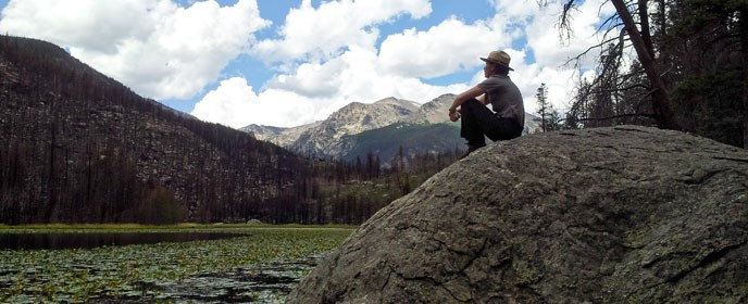A ranger sits next to a mountain lake