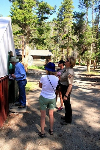 Carol Bell discusses one of the tent cabins with visitors