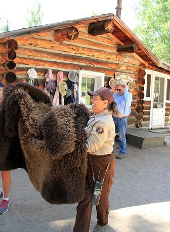 Jean Cross helps a visitor try on the buffalo coat